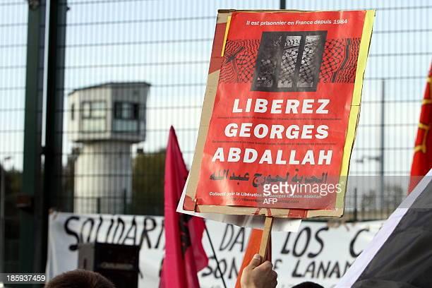 A man holds a sign reading 'Liberate Georges Abdallah' as he takes part in a protest calling for the liberation of Lebanese activist Georges Ibrahim...