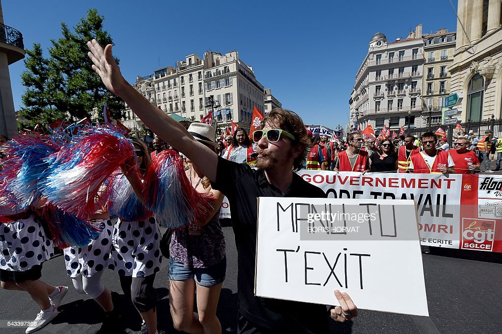 A man holds a sign reading 'Manu you exit' during a demonstration against the French government's planned labour law reforms, on June 28, 2016 in Marseille, southern France. Unions have called repeated strikes and marches in opposition to the law, which seeks to bring down France's intractable 10-percent unemployment rate by making it easier to hire and fire workers. / AFP / BORIS