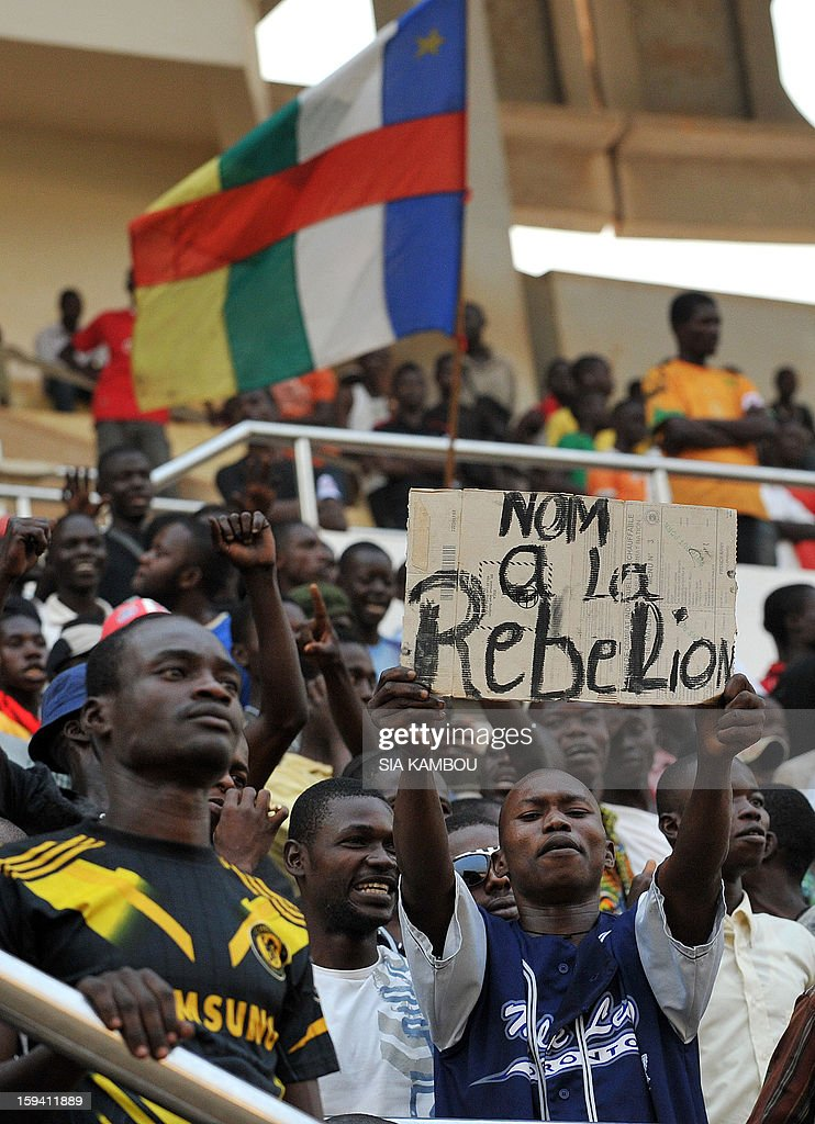 A man holds a sign reading 'No to the rebellion' amongst 'young patriots' who support the President of the Central African Republic Francois Bozize, as they rally before the president's arrival at the Bangui stadium, on January 13, 2013. Meanwhile Central African opposition lawyer Nicolas Tiangaye said today he has been named the country's new prime minister, after his predecessor was sacked to comply with a ceasefire deal reached with rebels.