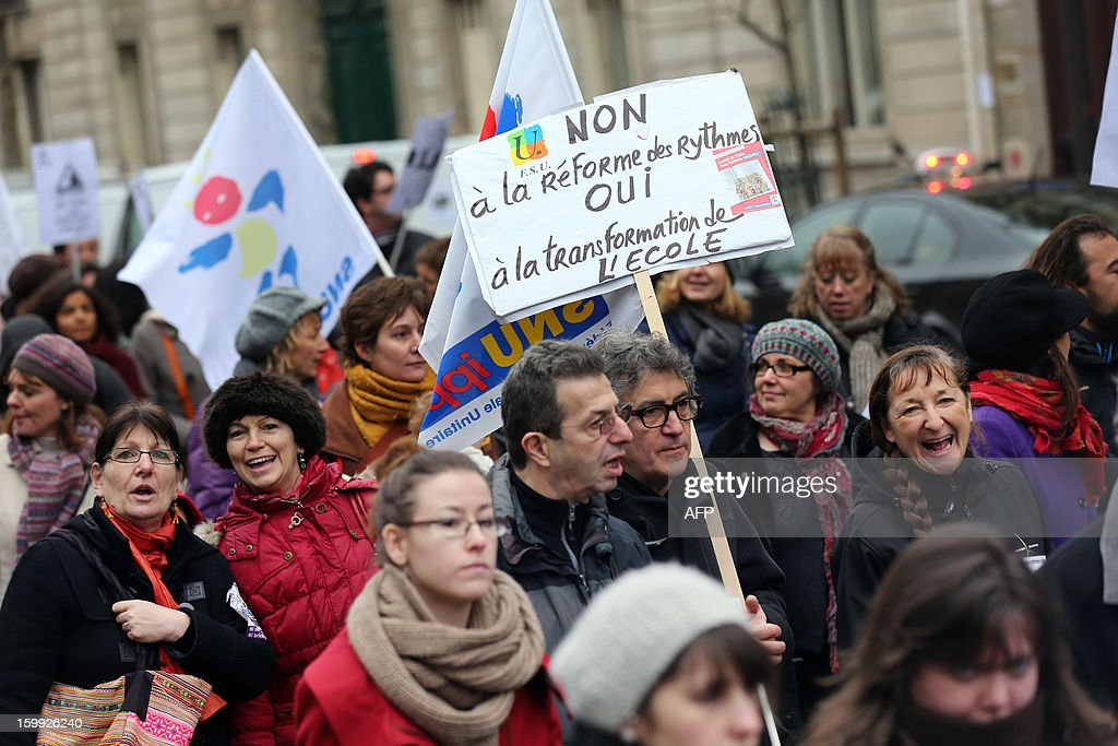 A man holds a sign reading 'NO to the reform of class hours, YES to school reforms', on January 23, 2013, in Paris, as he and other teachers take part in a nationwide strike and protest action against a proposed reform to increase the class time of primary school students. The strike and rally was called by French educational trade unions to protest a reform proposition by France's Education Minister, planned for the 2013-2014 schoolyear, which foresees an increase of class time in primary schools to 4.5 days a week and would affect both students and teachers. AFP PHOTO / THOMAS SAMSON