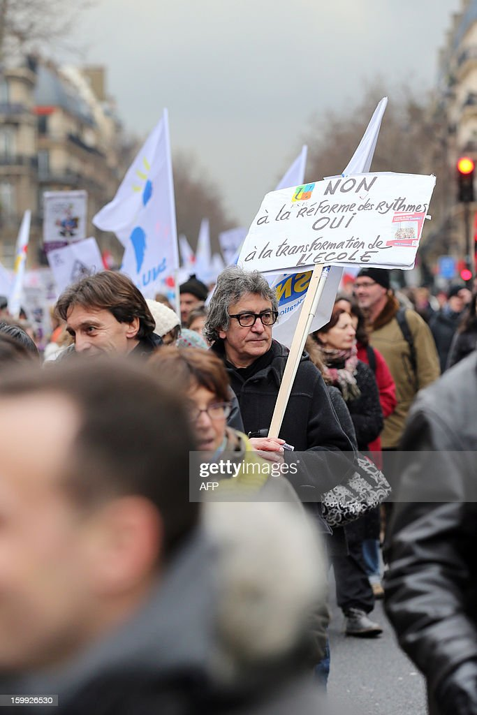 A man holds a sign reading 'NO to the reform of class hours, YES to school reforms', on January 23, 2013, in Paris, as he and other teachers take part in a nationwide strike and protest action against a proposed reform to increase the class time of primary school students. The strike and rally was called by French educational trade unions to protest a reform proposition by France's Education Minister, planned for the 2013-2014 schoolyear, which foresees an increase of class time in primary schools to 4.5 days a week and would affect both students and teachers.