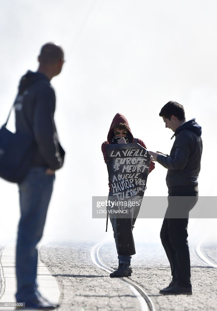 A man holds a sign reading 'Old Europe is dying' during a protest against the government's planned labour law reforms in Nantes, western France, on May 3, 2016. High school pupils and workers protested against deeply unpopular labour reforms that have divided the Socialist government and raised hackles in a country accustomed to iron-clad job security. / AFP / LOIC