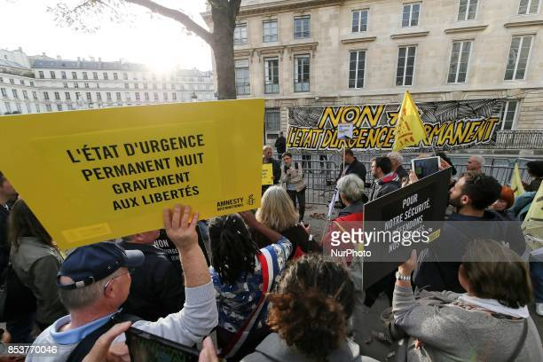 A man holds a sign reading 'permanent state of emergency hurts freedom' during a protest against 'permanent state of emergency' in Paris on September...