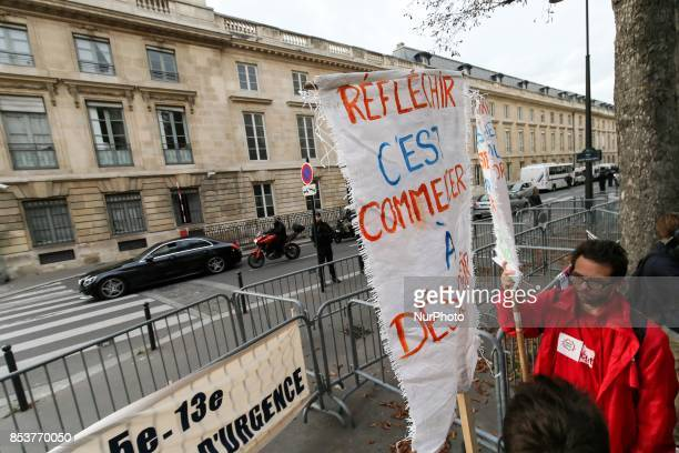 A man holds a sign reading 'permanent state of emergency makes radical permanent state of emergency terrorizes ' during a protest against 'permanent...
