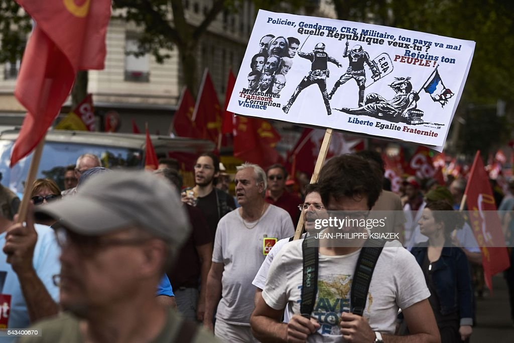 A man holds a sign reading 'Police, gendarme, anti-riot police, your country isn't well, which Republic do you want to? Join your people!' during a demonstration against controversial labour reforms, on June 28, 2016 in Lyon. Unions have called repeated strikes and marches in opposition to the law, which seeks to bring down France's intractable 10-percent unemployment rate by making it easier to hire and fire workers. / AFP / JEAN