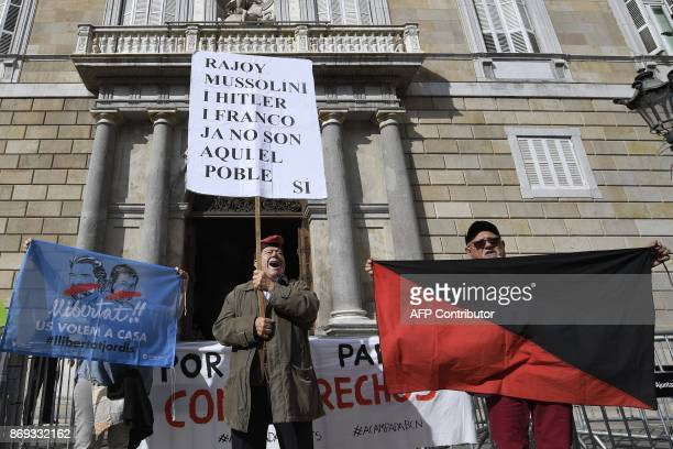 A man holds a sign reading 'Rajoy Mussolini Hitler and Franco are no longer here the people are' next to protesters holding an Iberian Anarchist...