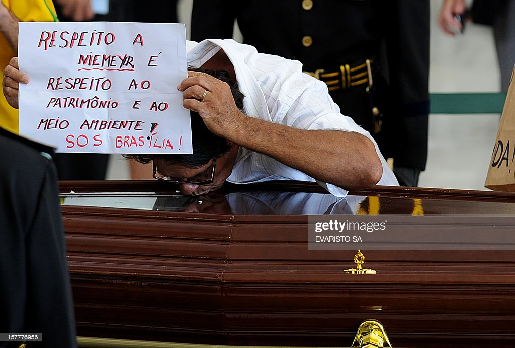 A man holds a sign reading 'Respect to Niemeyer is respect to heritage and environment' as he kisses the coffin of Brazilian architect Oscar Niemeyer during his funeral at Planalto Palace, in Brasilia, on December 6, 2012. Niemeyer, the Brazilian icon who revolutionized modern architecture and designed much of the country's futuristic capital Brasilia, died in Rio de Janeiro Wednesday at 104. The body will return to Rio de Janeiro for another funeral wake followed by the burial, according to Rio de Janeiro's Mayor Eduardo Paes. AFP PHOTO/Evaristo SA