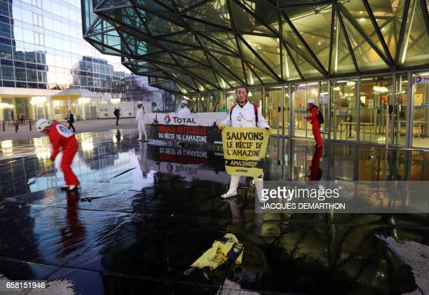 A man holds a sign reading 'Save the Amazon coral reef' as Greenpeace activisits pour molasse in front of French oil giant Total headquarters on...