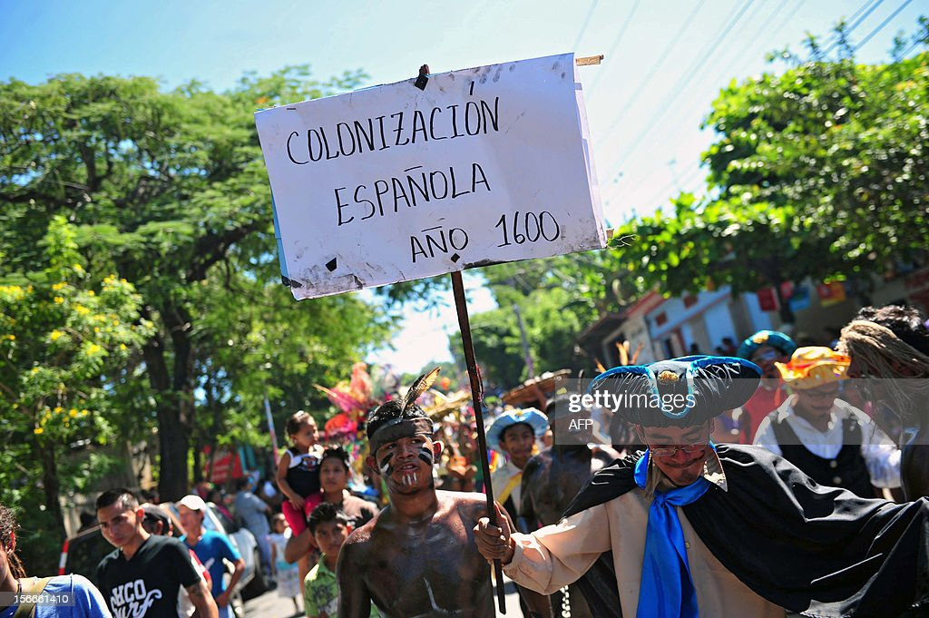 A man holds a sign reading 'Spanish Colonization. Year 1600' as he takes part in the 'Torovenado' carnival in the framework of the celebrations honouring Saint Jerome, the patron saint of Masaya, 30 km from Managua, on November 18, 2012. The festivities honouring Saint Jerome - the longest festivities in Nicaragua - began on September 20 and will end the last Sunday of November. AFP PHOTO/Hector RETAMAL
