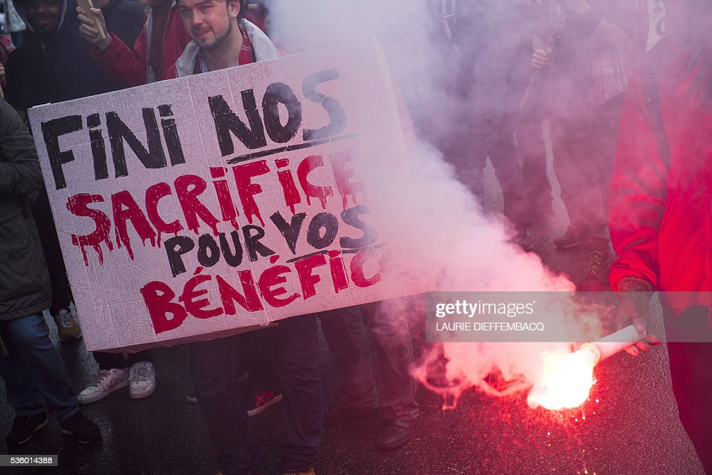 A man holds a sign reading 'Stop our sacrifices for your benefits' during a demonstration of the public sector staff against centre-right government's austerity plans, adding to ongoing strikes on the rail system and in prisons on May 31, 2016 in Brussels. Thousands of trade union members took part in peaceful protests in Brussels and other cities during the latest walkout at schools, city transport networks, airports and government offices. / AFP / BELGA / LAURIE DIEFFEMBACQ / Belgium OUT