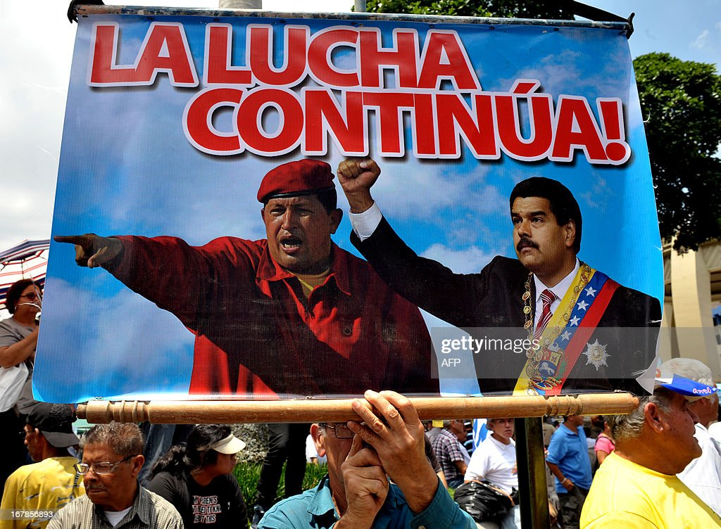 A man holds a sign reading 'The fight continues' with the images of former Venezuelan President Hugo Chavez (L) and Venezuelan new President Nicolas Maduro, during a May Day rally in San Jose on May 1, 2013. AFP PHOTO/Ezequiel BECERRA