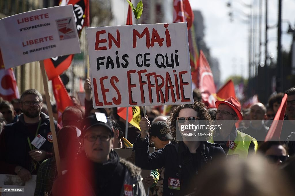 A man holds a sign reading 'This May do what scares them' during a May Day rally in Rennes, western France, on May 1, 2016. / AFP / DAMIEN