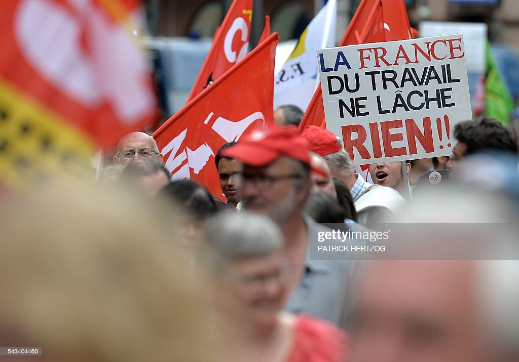 A man holds a sign reading 'Worker's France doesn't give up' during a demonstration against controversial labour reforms, on June 28, 2016 in Strasbourg, eastern France. Unions have called repeated strikes and marches against controversial labour reforms, forced through by the government of Socialist President Francois Hollande. / AFP / PATRICK