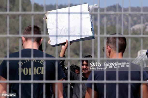 A man holds a sign saying 'We love you' as he protests at the detention center against his deportation to Turkey on April 5 2016 in Lesbos Greece...
