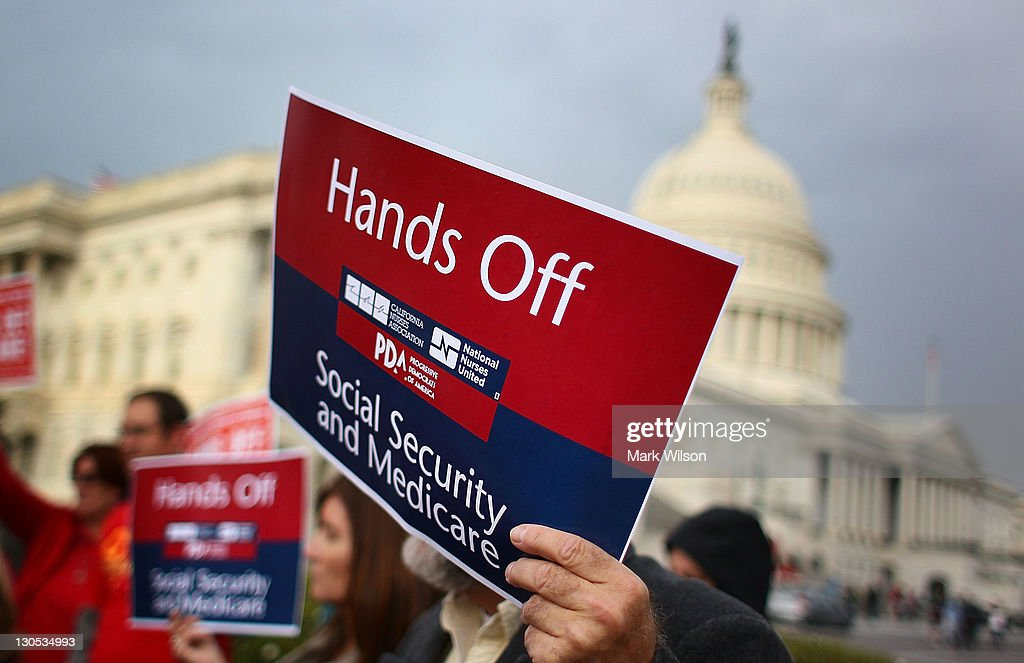 A man holds a sign that reads 'Hands Off Social Security and Medicare' during a news conference at the U.S. Capitol October 26, 2011 in Washington, DC. Members of Congress called on the Joint Deficit Reduction Committee to preserve Medicare, Medicaid, and Social Security benefits when making their decision on cutting the deficit.