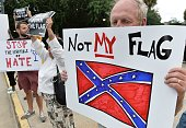 A man holds a sign up during a protest rally against the Confederate flag in Columbia South Carolina on June 20 2015 The racially divisive...