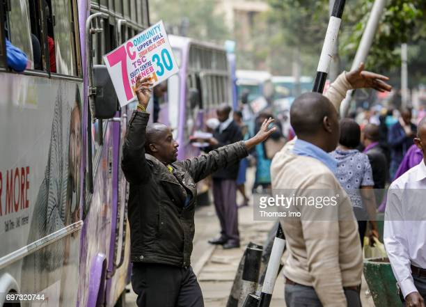 A man holds a signboard with information according the destination before the departure of a bus Street scene in Nairobi capital of Kenya on May 15...