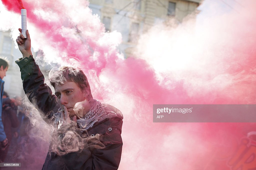 A man holds a smoke bomb during a protest by students against the local government in downtown Turin on December 14, 2013. Protesters clashed with police during anti-austerity demonstrations in Rome, Turin and Venice, as part of a wave of social action led by the 'Forconi' (Pitchforks) farmers and truck drivers movements.