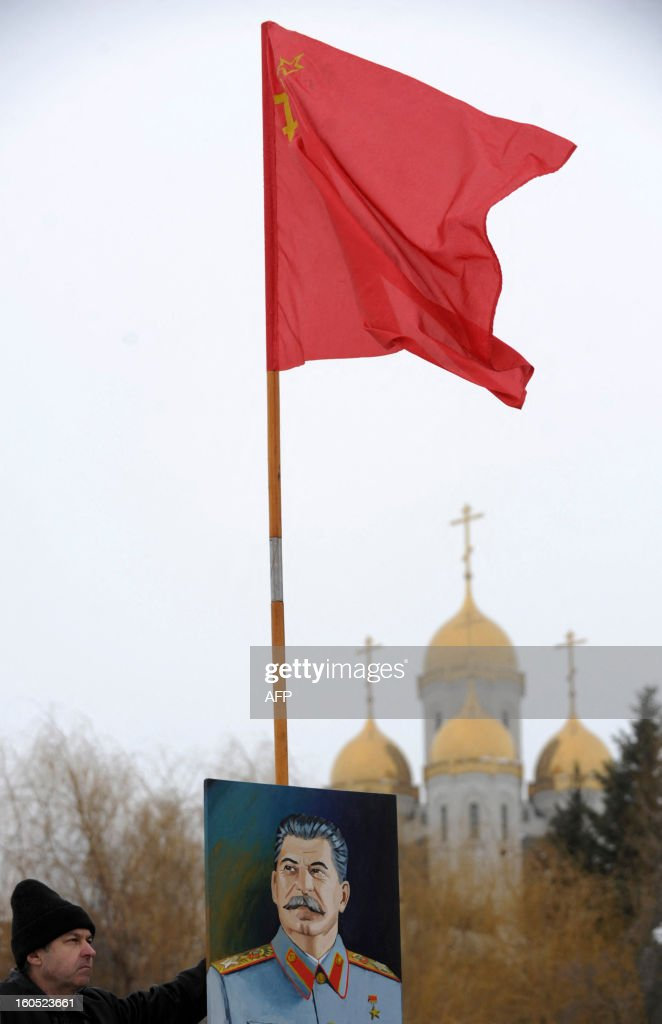 A man holds a Soviet red flag and portrait of the Soviet dictator Josef Stalin as he visits the memorial built to honour those who died in the Battle of Stalingrad during the World War II, in the Russian city of Volgograd, formerly Stalingrad, on February 2, 2013. Russia marked today the 70th anniversary of a brutal battle in which the Red Army defeated Nazi forces and changed the course of World War II. The pulverised city was renamed Volgograd in 1961 after Soviet leaders admitted the extent of Stalin's tyranny during his decades in power.