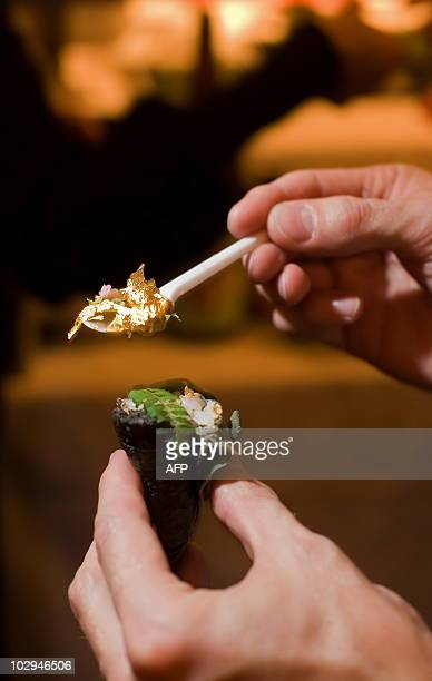 A man holds a spoon full of gold leaf ready to eat it with his sushi at the 'Seven Sushi Samurai' Sushi of the Year awards 2009 at the Olympia...