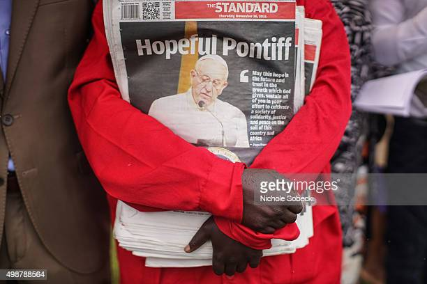 A man holds a stack of newspapers highlighting Pope Francis' visit to Kenya during a mass at the University of Nairobi grounds on November 26 in...