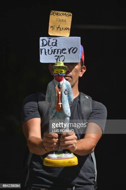 A man holds a statuette depicting Venezuelan physician Jose Gregorio Hernandez who is venerated by the Cathoplic Church and a sign reading 'Day...