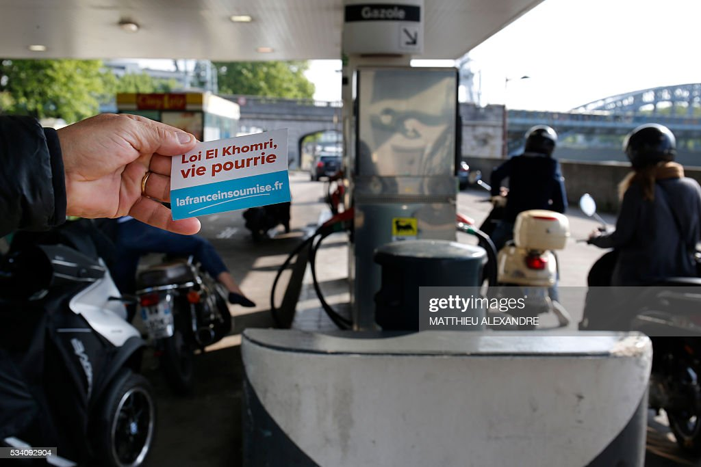 A man holds a sticker reading 'El Khomri's law, rotten life' as people queue to refill their tank on May 25, 2016 in Paris. France has been using strategic fuel reserves for two days in the face of widespread blockades of oil depots by union activists, the head of the oil industry federation said on May 25, 2016. ALEXANDRE