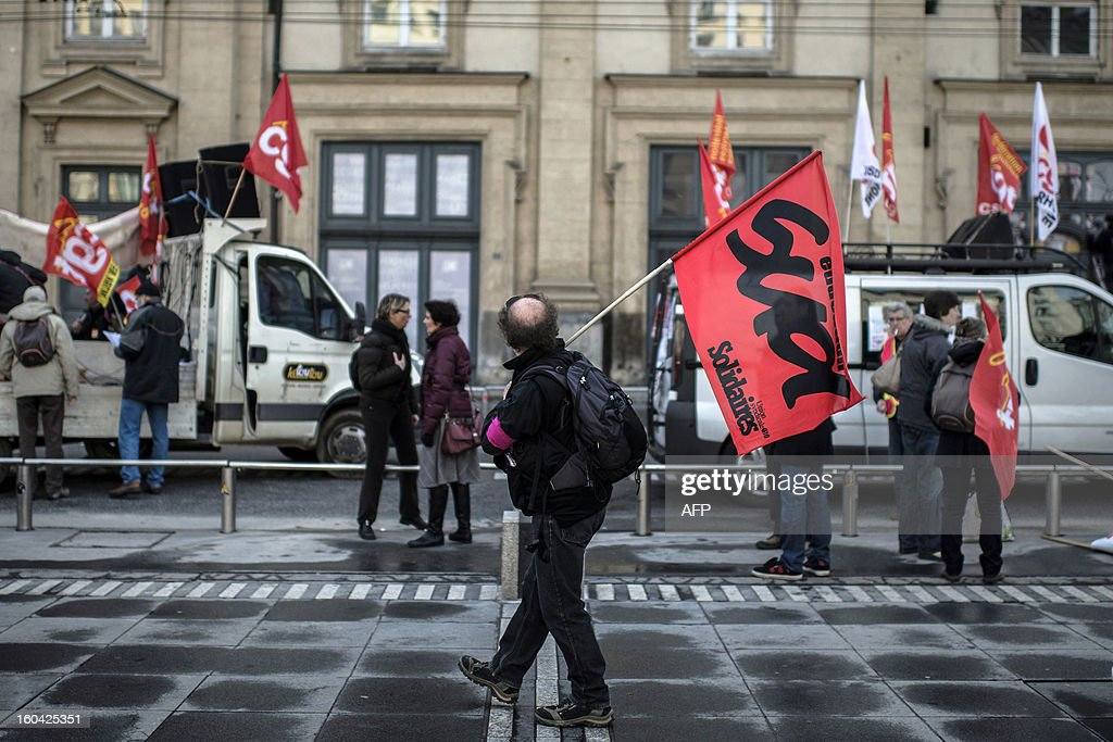 A man holds a Sud union's flag as members of the public sector, (education, health and finance) take part on January 31, 2013 in a national day of protest in Lyon against the French government's social policy. For the first time since French President Francois Hollande's election, three labour unions (CGT, FSU, Solidaires) called on 5.2 million civil servants to stop working to show to the government their unhappiness, particularly in terms of purchasing power.