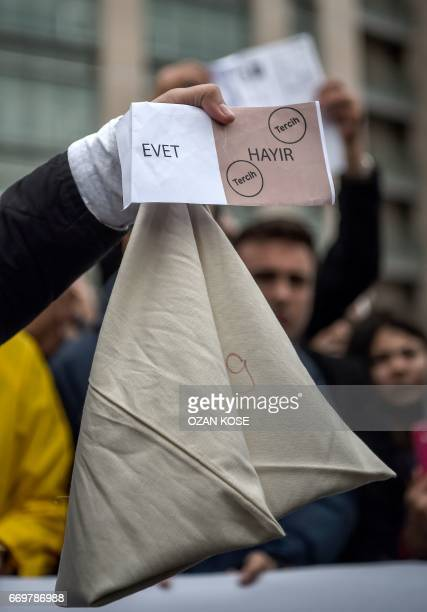 A man holds a symbolic vote ballot and a mark ballot paper showing two 'my choice' stamps in the 'No' leaving the 'Yes' section blank as members of...