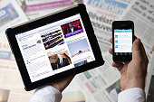 A man holds a tablet and a smartphone showing a news website and a Twitter news thread in front of world newspapers on September 12 2013 in Paris AFP...