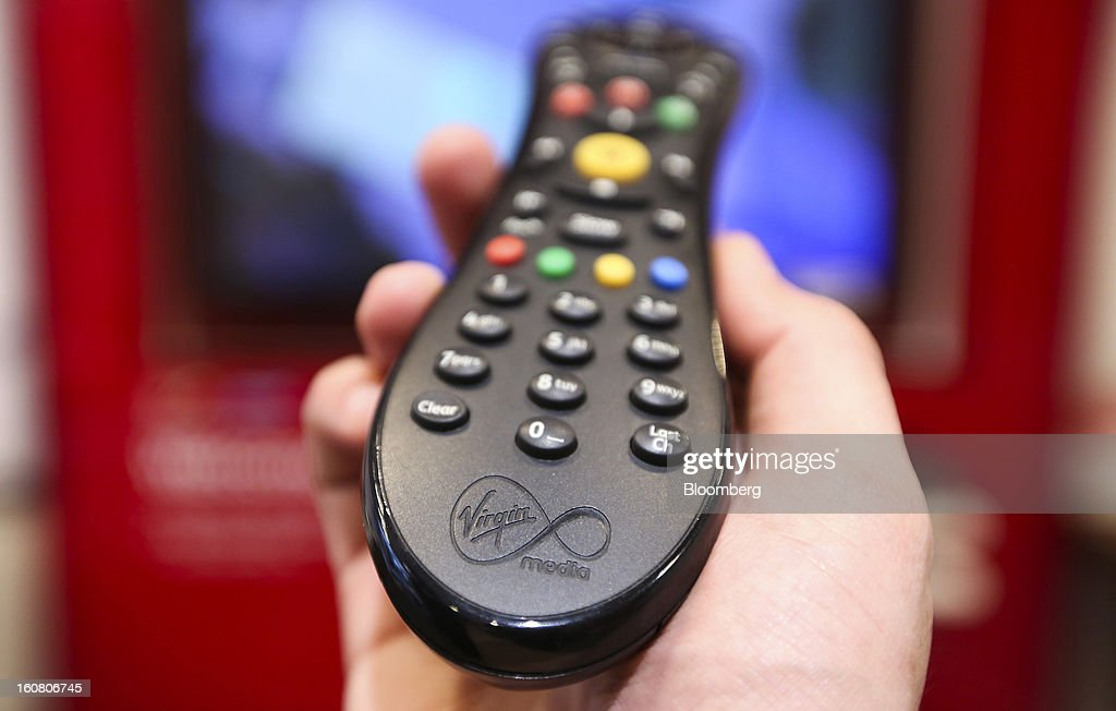 A man holds a television remote control unit for a Virgin Media set top box in this arranged photograph at the company's store on Oxford Street in London, U.K., on Wednesday, Feb. 6, 2013. Billionaire John Malone's Liberty Global Inc. agreed to acquire Virgin Media, Britain's second-largest pay-TV provider, in a $16 billion cash-and-stock transaction announced in the U.S. yesterday. Photographer: Chris Ratcliffe/Bloomberg via Getty Images