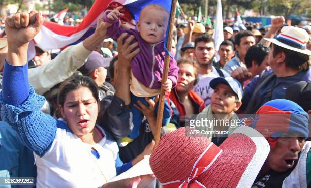 A man holds a toddler during a farmers protest in downtown Asuncion demanding the writing off of their debts on August 9 2017 Farmers are facing...
