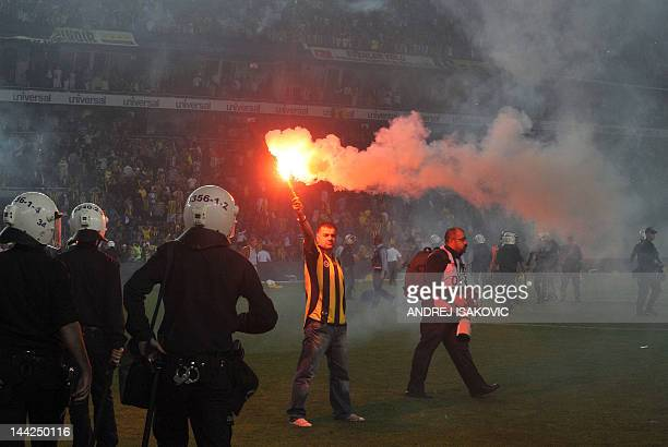 A man holds a torch during clashes between Fenerbahce's supporters and police officers after their Turkish Super League playoff final football match...