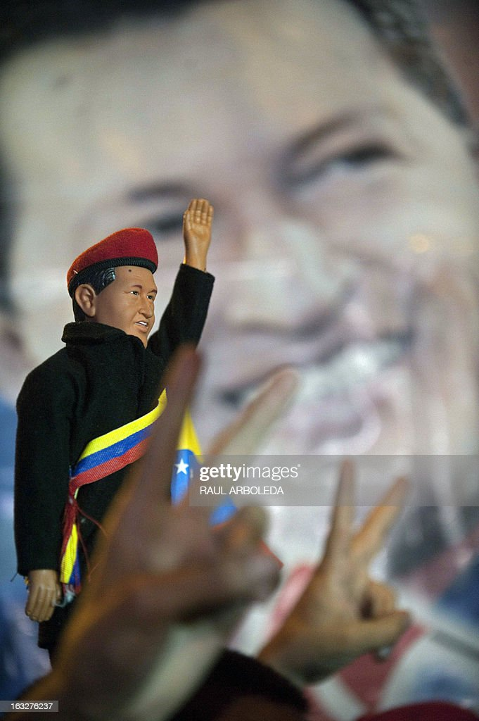 A man holds a toy with the image of Venezuelan President Hugo Chavez outside the Venezuelan embassy in Bogota, Colombia on March 6, 2013, after Venezuelan President Hugo Chavez's death. The flag-draped coffin of Venezuelan leader Hugo Chavez was borne through throngs of weeping supporters on Wednesday as a nation bade farewell to the firebrand leftist who led them for 14 years. AFP PHOTO / Raul ARBOLEDA