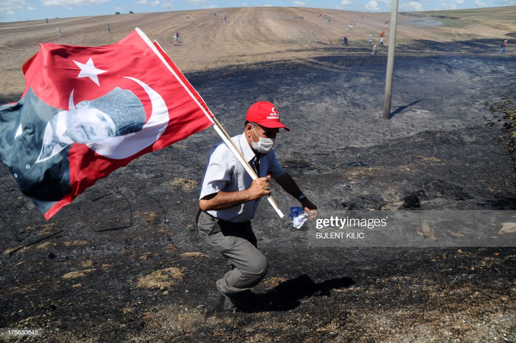 A man holds a Turkish flag bearing a portrait of the late founder of modern Turkey Mustafa Kemal Ataturk while he runs away across burned fields during clashes between Turkish police and protestors on August 5, 2013, as police and gendarmerie block the way to a courthouse in Silivri, near Istanbul, where prosecutors are scheduled to deliver their final arguments in the case against 275 people accused of plotting to overturn the Islamic-leaning government. Among the defendants in the high-profile case -- seen as a key test in Prime Minister Recep Tayyip Erdogan's showdown with secularist and military opponents -- are ex-military chief Ilker Basbug and other army officers as well as lawyers, academics and journalists. AFP PHOTO/BULENT KILIC