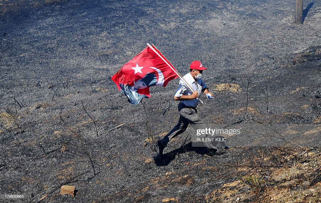 A man holds a Turkish flag bearing a portrait of the late founder of modern Turkey Mustafa Kemal Ataturk while he runs away across burned fields during clashes between Turkish police and protestors on August 5, 2013, as police and gendarmerie block the way to a courthouse in Silivri, near Istanbul, where prosecutors are scheduled to deliver their final arguments in the case against 275 people accused of plotting to overturn the Islamic-leaning government. Among the defendants in the high-profile case -- seen as a key test in Prime Minister Recep Tayyip Erdogan's showdown with secularist and military opponents -- are ex-military chief Ilker Basbug and other army officers as well as lawyers, academics and journalists.