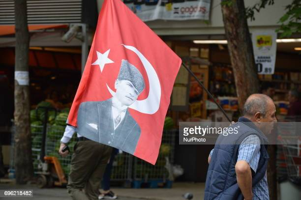 A man holds a Turkish flag with the portrait of Mustafa Kemal Ataturk before the 'Justice March' to protest against the Turkish government held by...