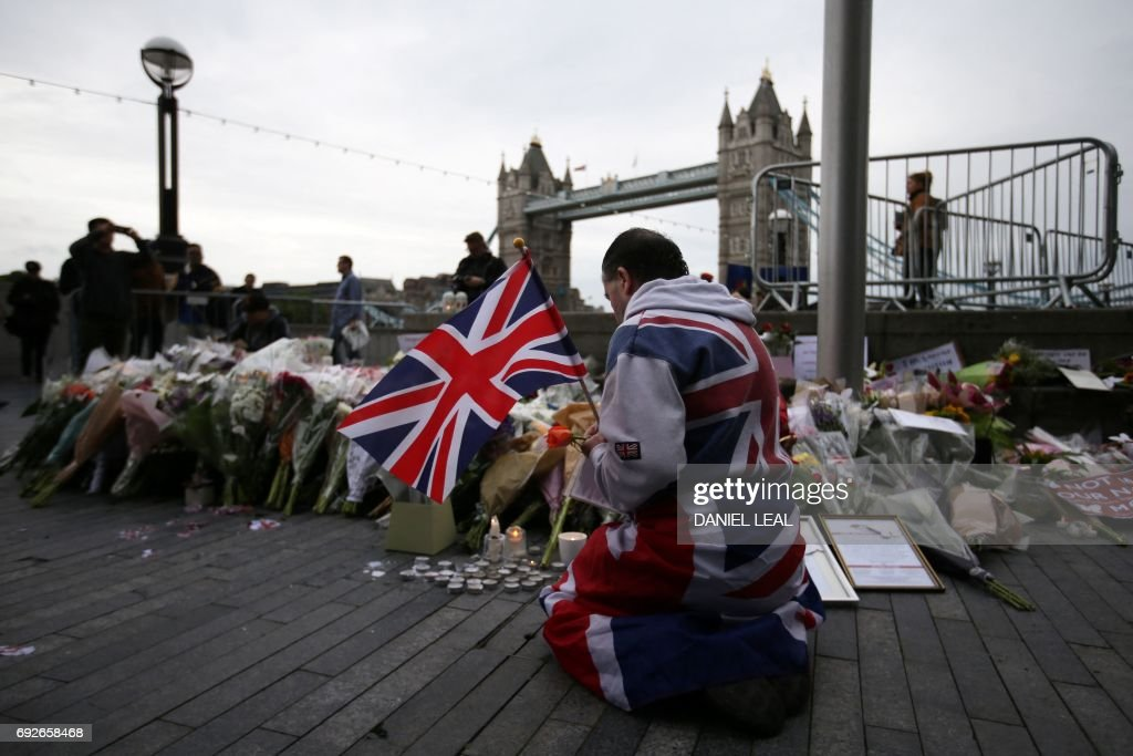 TOPSHOT - A man holds a Union flag as he kneels near flowers layed at Potters Fields Park in London on June 5, 2017, during a vigil to commemorate the victims of the terror attack on London Bridge and at Borough Market that killed seven people on June 3. London police made a fresh round of arrests on June 5 after the country's third terror attack in less than three months as Prime Minister Theresa May came under mounting pressure over security three days ahead of elections. The aftermath of June 3 night's rampage, which left seven dead and dozens wounded, dominated the campaign trail. PHOTO / Daniel LEAL