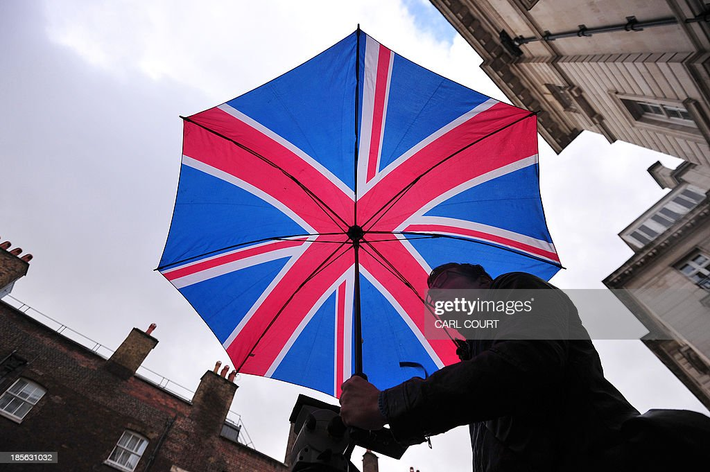 A man holds a Union Flag umbrella as he waits opposite St James's Palace in central London on October 23, 2013, where Prince George of Cambridge will be baptised later in the day inside Chapel Royal. Prince William and his wife Catherine gather close friends and family for the christening of their baby son Prince George, in a low-key ceremony far removed from the global hype surrounding their wedding.