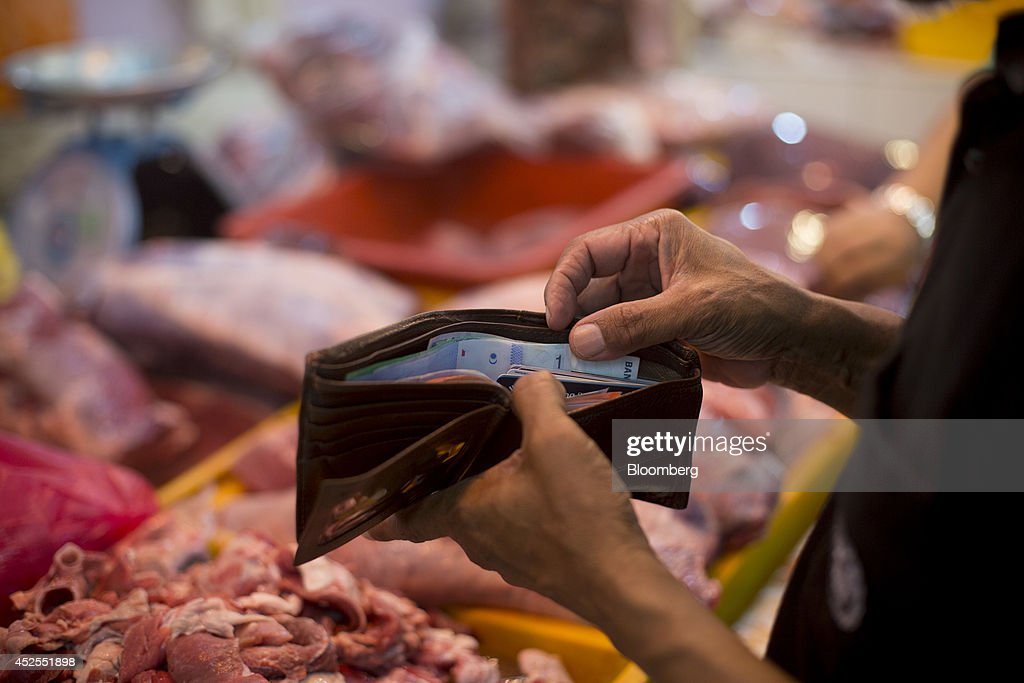 A man holds a wallet containing Malaysian ringgit banknotes in front of a meat stall at the Chow Kit wet market in Kuala Lumpur, Malaysia, on Tuesday, July 22, 2014. Malaysian Airline System Bhd. (MAS), reeling from its second disaster in four months, plans to present a revival plan to its state-run parent Khazanah Nasional Bhd. this week, people familiar with the matter said, amid reports the national carrier is likely near the end of its days as a publicly traded company. Photographer: Brent Lewin/Bloomberg via Getty Images