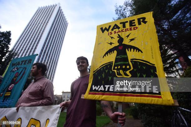 A man holds a 'Water is Sacred' sign as protesters stand in solidarity with the 'Native Nations Rise' march on Washington DC against the construction...
