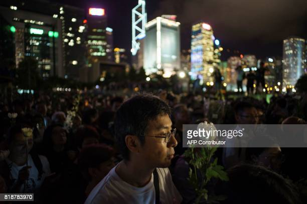 A man holds a white flower at a memorial event for the late Chinese Nobel laureate Liu Xiaobo in Hong Kong on July 19 2017 Hundreds turned out in...
