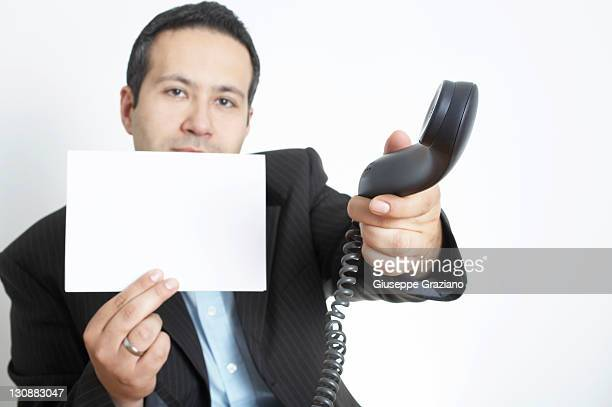 Man holds a white sheet of paper, catching the telephone receiver
