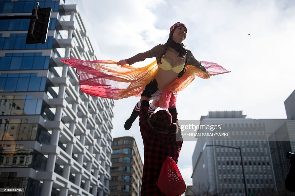 A man holds a woman up while running in 'Cupid's Undie Run' to raise money for charity on February 13, 2016 in Washington, DC. Participants run in their Valentine's-themed underwear, raising funds for the Children's Tumor Foundation. The temperature high on Saturday reached 20 degrees Fahrenheit (-6.6 Celsius). / AFP / Brendan Smialowski