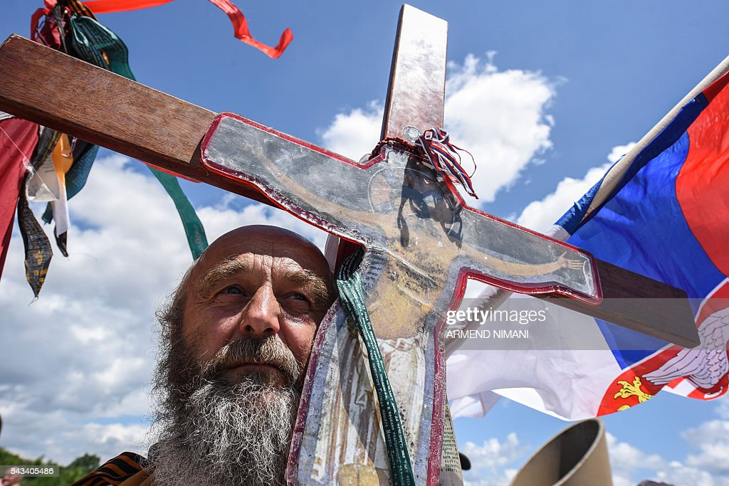 A man holds a wooden cross stands before the Gazimestan memorial, near the village of Mazgit, Kosovo, as people take part in a ceremony marking the historic 'Battle of Kosovo', on June 28, 2016. The ceremony marks the Battle of Kosovo in 1389 when the Serbian army was defeated by the Ottoman Empire. / AFP / ARMEND