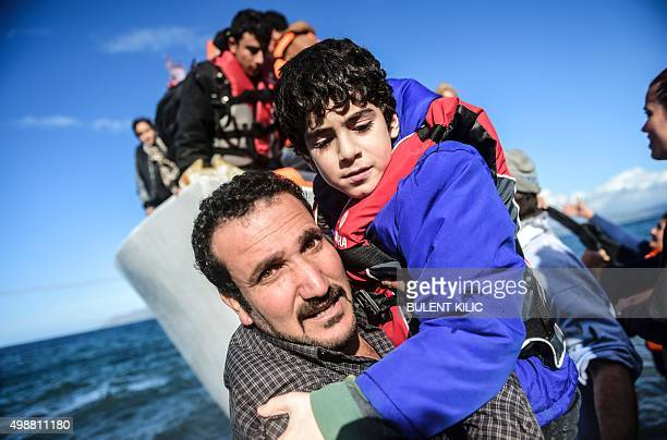 A man holds a young boy as migrants and refugees arrive on the Greek island of Lesbos after crossing the Aegean Sea from Turkey on November 26 2015...