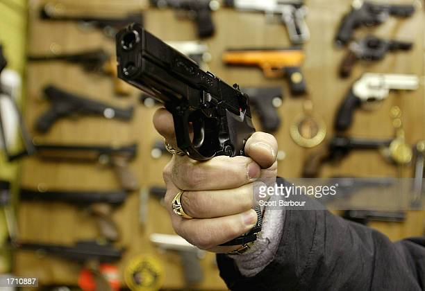 A man holds an Airsoft plastic BB gun in front of a shop display of the hobbyist replica firearms January 6 2003 in London British Home Secretary...