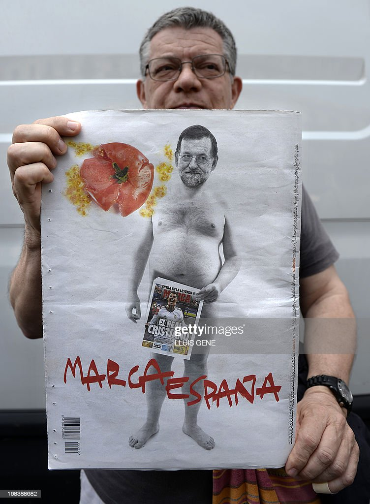 A man holds an alternative newspaper depicting on his back page a montage of a naked Spanish Prime Minister and PP (Popular Party) leader Mariano Rajoy hiding his sex with the front page of Spanish sports newspaper 'Marca' with a picture of Real Madrid's Portuguese forward Cristiano Ronaldo during a demonstration against the government's cuts to education spending near the headquarters of the Catalan government, the Palau de la Generalitat, in Barcelona on May 9, 2013.