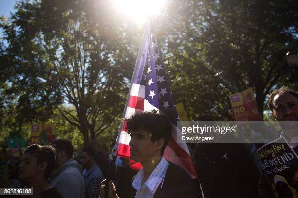 A man holds an American flag during a protest against the Trump administration's proposed travel ban October 18 2017 in Washington DC Early Wednesday...