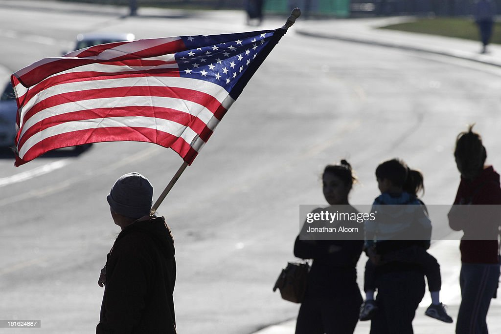 A man holds an American flag outside the funeral for Riverside police Officer Michael Crain at Grove Community Church February 13, 2013 in Riverside, California. Crain was allegedly killed by the former Los Angeles Police Department officer Chris Dorner on February 7, 2013.